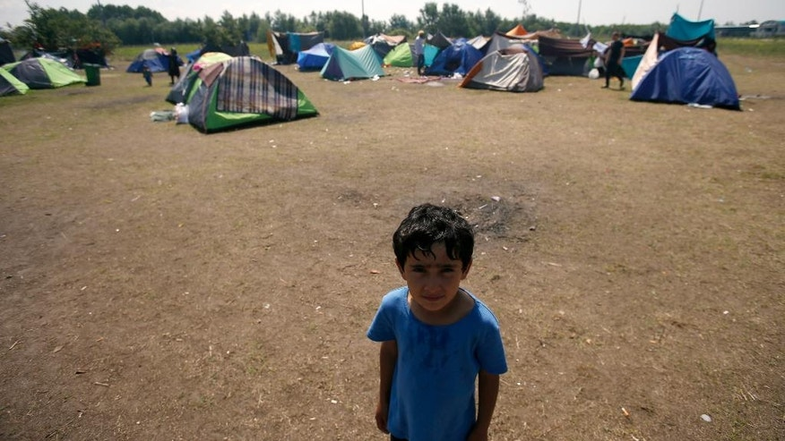 A boy stands in the makeshift refugee camp near the Horgos border crossing into Hungary, near Horgos, Serbia, Friday, May 27, 2016. Nearly 400,000 refugees passed through Hungary last year on their way to richer EU destinations. The flow was slowed greatly by Hungary's construction of razor-wire fences on its borders with Serbia and Croatia. (AP Photo/Darko Vojinovic)