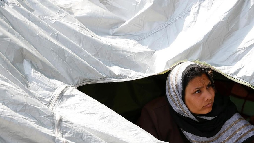 A woman looks out from her tent in the makeshift refugee camp near the Horgos border crossing into Hungary, near Horgos, Serbia, Friday, May 27, 2016. Nearly 400,000 refugees passed through Hungary last year on their way to richer EU destinations. The flow was slowed greatly by Hungary's construction of razor-wire fences on its borders with Serbia and Croatia. (AP Photo/Darko Vojinovic)