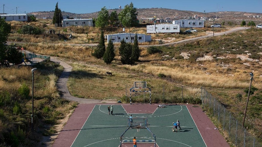 In this Wednesday, May 18, 2016 photo, Jewish settler youths play soccer in Amona, an unauthorized Israeli outpost in the West Bank, east of the Palestinian town of Ramallah. It is the largest of about 100 outposts in the West Bank which were built without permission but generally tolerated by the government. Under an Israeli Supreme Court order, the government must tear down the outpost by the end of 2016. (AP Photo/Oded Balilty)