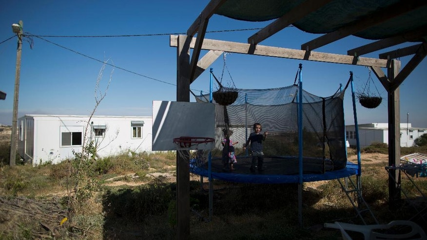 In this Wednesday, May 18, 2016 photo, Jewish settler children jump on a trampoline in Amona, an unauthorized Israeli outpost in the West Bank, east of the Palestinian town of Ramallah. It is the largest of about 100 outposts in the West Bank which were built without permission but generally tolerated by the government. Under an Israeli Supreme Court order, the government must tear down the outpost by the end of 2016. (AP Photo/Oded Balilty)