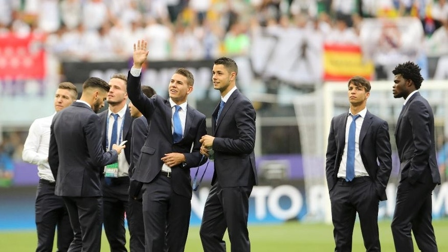 Atletico Madrid players walk on the pitch and wave to fans, prior to the Champions League final soccer match between Real Madrid and Atletico Madrid at the San Siro stadium in Milan, Italy, Saturday, May 28, 2016.  (AP Photo/Luca Bruno)