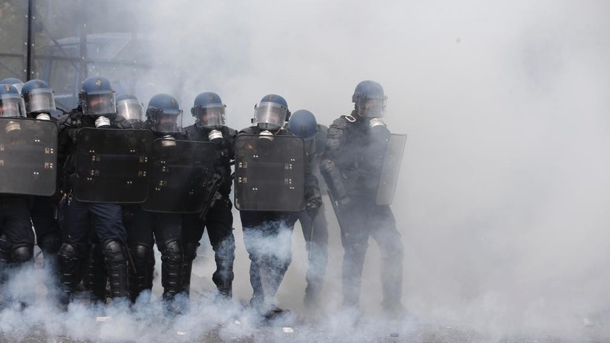 Riot police officers take position amid tear gas smoke during a demonstration held as part of nationwide labor actions in Paris, Thursday, May 26, 2016. French protesters scuffled with police, dock workers set off smoke bombs and union activists disrupted fuel supplies and nuclear plants Thursday in the biggest challenge yet to President Francois Hollande's government as it tries to give employers more flexibility. (AP Photo/Thibault Camus)