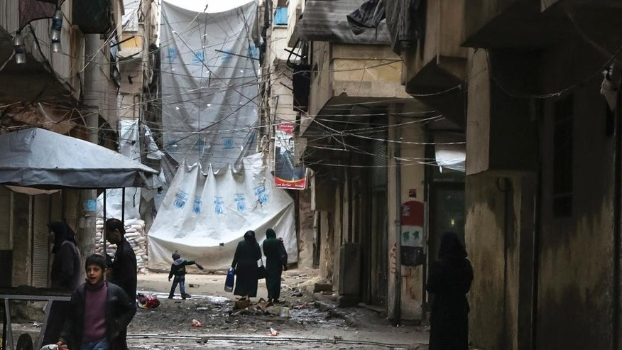 FILE - In this Thursday, Feb. 11, 2016 file photo, civilians walk through a street with large tarps are hung in between building to limit the view of regime snipers in Aleppo, Syria. Islamic State militants entered a Syrian opposition stronghold in the country's north on Saturday, clashing with rebels on the edges of the town as the extremist group built on its most significant advance near the Turkish border in two years, Syrian opposition groups and IS media said. (Alexander Kots/Komsomolskaya Pravda via AP, File)