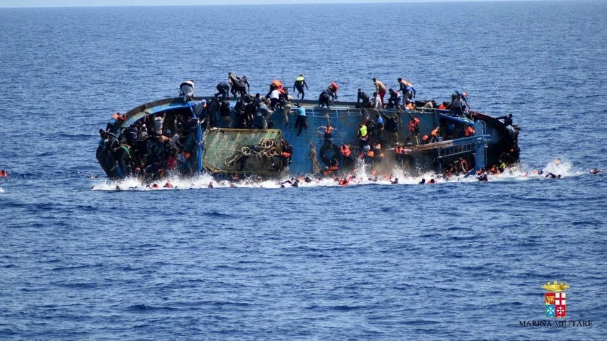 People jump off a boat moments before it overturns off the Libyan coast, Wednesday, May 25, 2016. On Friday, the Italian navy says it has saved 135 migrants and recovered 45 bodies. (Marina Militare via AP)