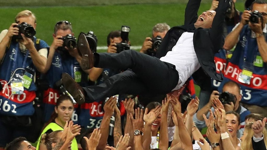 Real Madrid's head coach Zinedine Zidane is thrown into the air in celebration after the Champions League final soccer match between Real Madrid and Atletico Madrid at the San Siro stadium in Milan, Italy, Saturday, May 28, 2016. Real Madrid won 5-4 on penalties after the match ended 1-1 after extra time.  (AP Photo/Alessandra Tarantino)