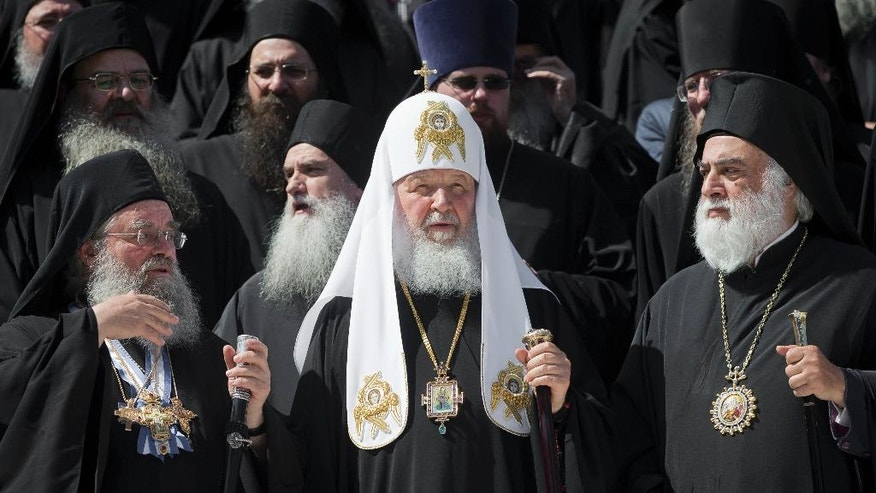Patriarch Kirill of Moscow, center, poses for cameras with orthodox monks in Karyes, the capital of Mount Athos, Greece, Friday, May 27, 2016, ahead of Russia's president Putin visit. Russia's president is due in financially struggling Greece Friday for a state visit that will include a trip to a 1,000-year-old, all-male Orthodox Christian sanctuary in the north of the country. (AP Photo/Darko Bandic)