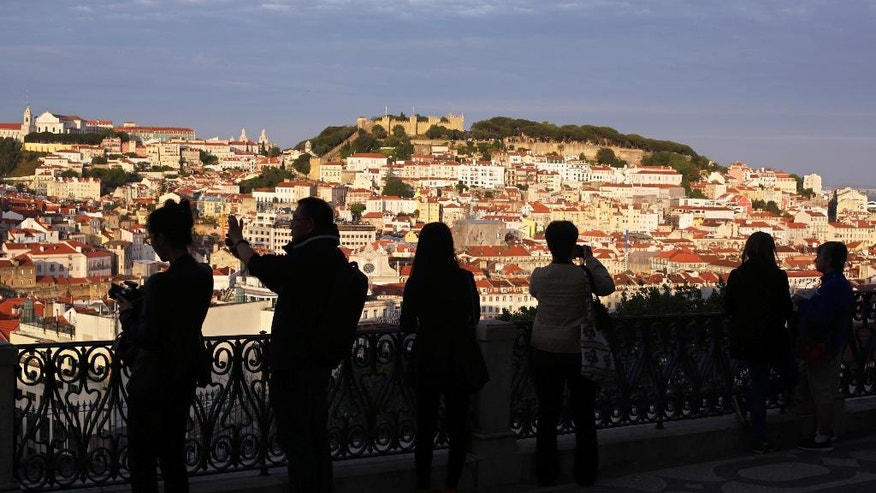 In this May 25, 2016 photo, tourists taking pictures are silhouetted against Lisbon's old center lit by the setting sun. With sunny days getting longer and lazier, sparkling beaches warming up and terrorism fears driving customers away from other Mediterranean destinations, Spain and Portugal are reaping an economic bonanza from tourism. (AP Photo/Armando Franca)