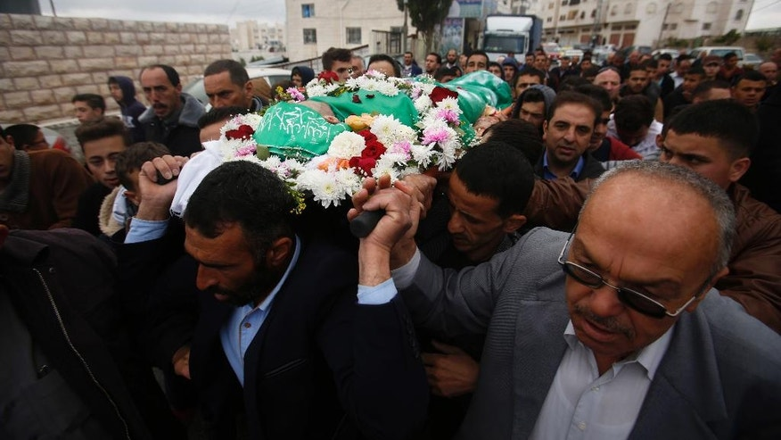 Palestinians chant slogans as they carry the body of Abdel-Fattah al-Sharif, during his funeral, in the West Bank city of Hebron, Saturday, May 28, 2016. Al-Sharif was killed by an Israeli soldier in March while lying on the ground seriously wounded after he and another Palestinian attacked IDF troops.(AP Photo/Nasser Shiyoukhi)