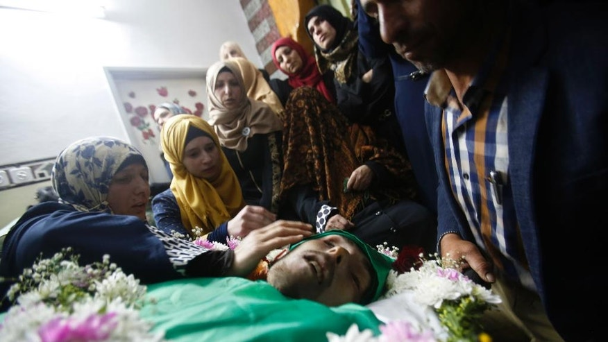 The mother, left, and relatives gather around the body of Palestinian Abdel-Fattah al-Sharif, during his funeral, in the West Bank city of Hebron, Saturday, May 28, 2016. Al-Sharif was killed by an Israeli soldier in March while lying on the ground seriously wounded after he and another Palestinian attacked IDF troops. (AP Photo/Nasser Shiyoukhi)