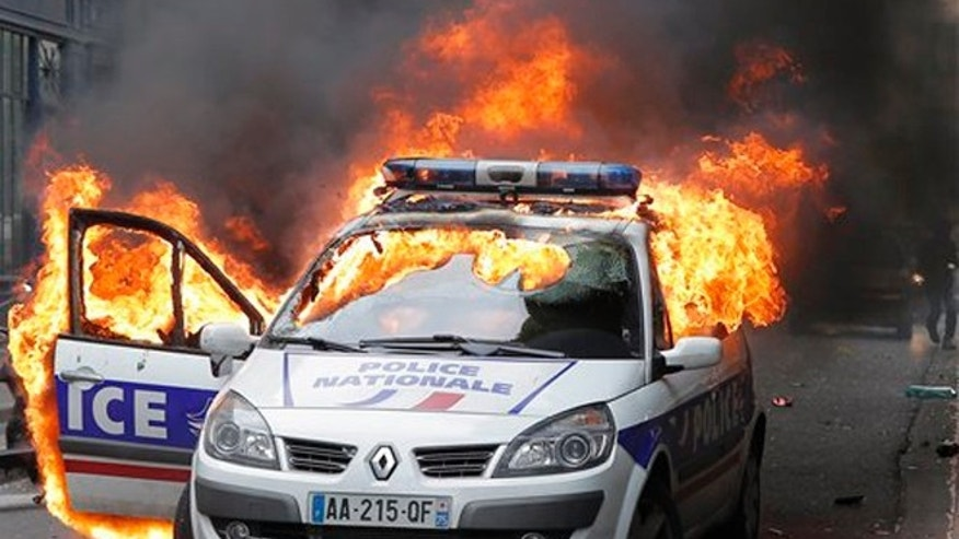 In this Wednesday, May 18, 2016 file picture, A police car burns during clashes while police forces gather to denounce the hatred and violence they say is being repeatedly directed at them during near-daily protests against labor reforms, in Paris.