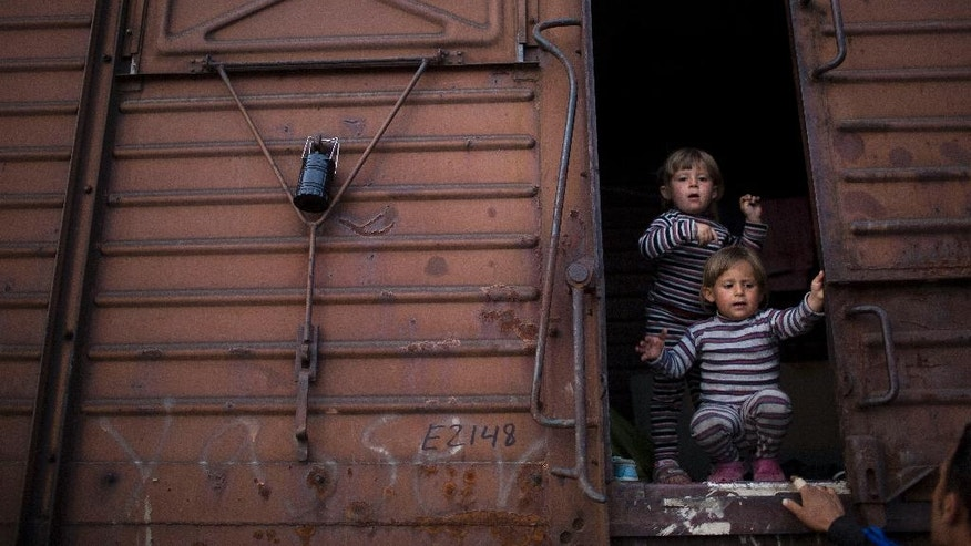 FILE - In this Tuesday, May 10, 2016 file photo two Syrian twin sisters chat with a relative as they stand inside a freight car that their family live in the sprawling refugee and migrant tent city of Idomeni, on Greece's northern border with Macedonia. On government orders, Idomeni was cleared this week. Just before the evacuation Idomeni had 8,400 occupants, according to official figures, and it's unclear where all those who didn't get the buses to other camps are. (AP Photo/Petros Giannakouris)