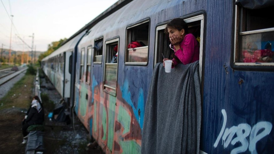 In this Saturday, May 7, 2016 photo, a Syrian girl looks out train window that she lives with her family in the sprawling refugee and migrant tent city of Idomeni, on Greece's northern border with Macedonia. The evacuation of Idomeni has dashed the dreams of thousands migrants and refugees who had been camping there for months in the hopes of eventually being able to cross over the border and continue toward Europe's more prosperous heartland.(AP Photo/Petros Giannakouris)