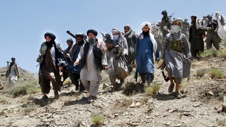 In this Friday, May 27, 2016 photo, the senior leader of a breakaway faction of the Taliban Mullah Abdul Manan Niazi, second left, arrives to give a speech to his fighters, in Shindand district of Herat province, Afghanistan. Niazi said Sunday, May 29, 2016 it was willing to hold peace talks with the Afghan government but would demand the imposition of Islamic law and the departure of all foreign forces. (AP Photos/Allauddin Khan)