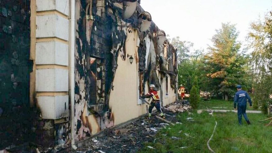 In this Sunday, May 29, 2016 photo, supplied by the Ukrainian Emergency Situations Ministry Press Service, emergency ministry employees search a site of a fire at Litchi, Kiev region, Ukraine. Ukraine's emergency services say a fire has swept through a private home for the aged, killing over a dozen of the 35 residents and injured five others. No cause has yet been determined for the fire that broke out early Sunday in Litochki, a village 42 kilometers (25 miles) north of Kiev, the capital. (Ukrainian Emergency Situations Ministry Press Service Photo via AP)