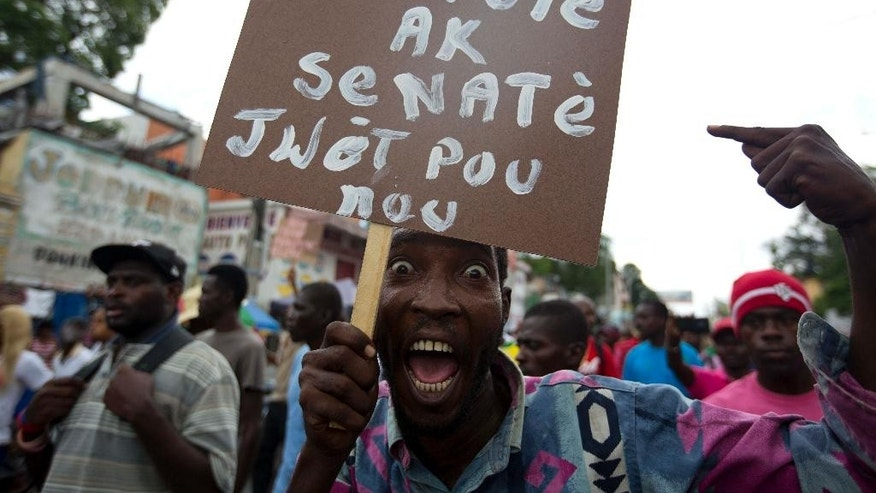 "FILE - In this May 14, 2016 file photo, a supporter of the PHTK presidential candidate Jovenel Moise holds up a handmade sign with a message that reads in Creole; ""Deputies and senators the responsibility is yours"" during a protest march demanding the resignation of interim President Jocelerme Privert in Port-au-Prince, Haiti. Haitians are bracing for trouble as an electoral verification commission is due to deliver on Sunday, May 29, 2016, the results of its month-long review of last year's presidential and legislative elections that have been repeatedly derided as a sham. (AP Photo/Dieu Nalio Chery, File)"