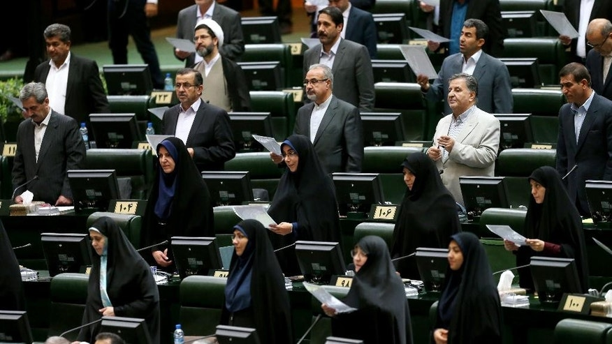 Iranian lawmakers take an oath during the inauguration of the new parliament, in Tehran, Iran, Saturday, May 28, 2016. Moderate candidates and supporters of President Hassan Rouhani secured majority of seats in the new parliament. (AP Photo/Ebrahim Noroozi)