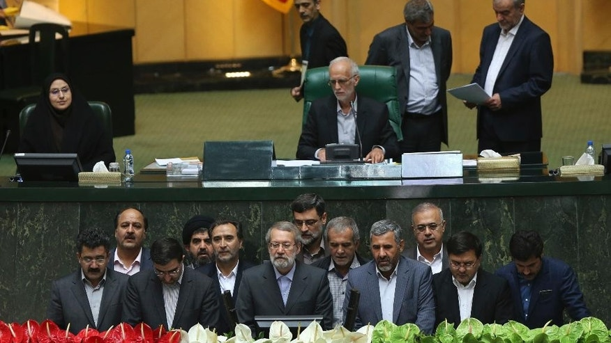 Interim presiding board of Iran's new parliament, bottom, including speaker Ali Larijani, bottom center, take an oath in an open session of the parliament in Tehran, Iran, Sunday, May 29, 2016. Iran's long-serving parliament speaker Larijani will retain his post despite gains by reformists in elections held earlier this year, the official IRNA news agency reported Sunday. (AP Photo/Vahid Salemi)
