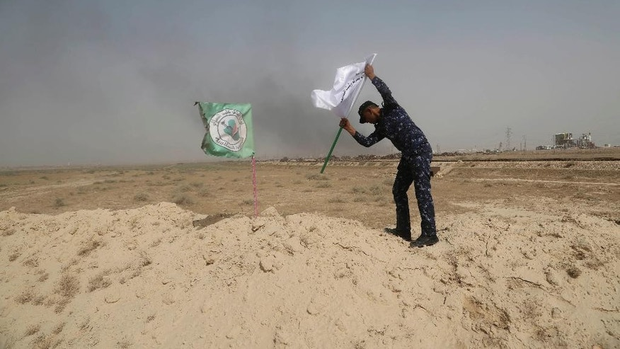 A policeman places an Iraqi federal police flag next to a Shiite Popular Mobilization Forces flag during a fight against Islamic State militants outside Fallujah, Iraq, Saturday, May 28, 2016. Days into an Iraqi military operation to push Islamic State fighters out of Fallujah, residents still inside the city are preparing for a long battle, with some saying they fear being trapped between two forces they don't fully trust.(AP Photo/Khalid Mohammed)
