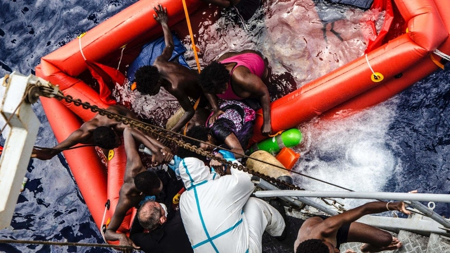 In this photo taken in the Mediterranean Sea, off the Libyan coast, Friday, May 27, 2016 rescuers help migrants to board the Italian Navy ship Vega, after the boat they were aboard sunk.