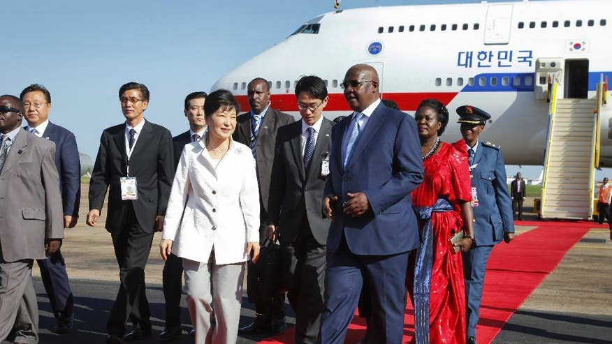 South Korea's president Park Geun-hye, center-left, is greeted by Uganda's Foreign Affairs Minister Sam Kutesa, center-right, after arriving at the airport in Entebbe, Uganda Saturday, May 28, 2016. South Korea's president has arrived in Uganda for a two-day state visit during which she is expected to discuss business and trade opportunities, the first such visit by a South Korean president since the two countries established diplomatic ties in 1963. (AP Photo/Stephen Wandera)