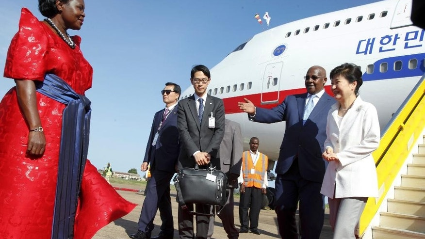 South Korea's president Park Geun-hye, right, is greeted by Uganda's Foreign Affairs Minister Sam Kutesa, 2nd-right, and Uganda's Chief Government Whip Ruth Nankabirwa, left, after arriving at the airport in Entebbe, Uganda Saturday, May 28, 2016. South Korea's president has arrived in Uganda for a two-day state visit during which she is expected to discuss business and trade opportunities, the first such visit by a South Korean president since the two countries established diplomatic ties in 1963. (AP Photo/Stephen Wandera)