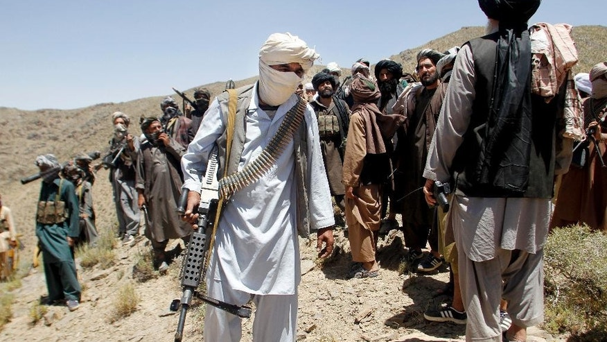 In this Friday, May 27, 2016 photo, members of a breakaway faction of the Taliban fighters walks during a gathering, in Shindand district of Herat province, Afghanistan. Mullah Abdul Manan Niazi said Sunday, May 29, 2016 he was willing to hold peace talks with the Afghan government but would demand the imposition of Islamic law and the departure of all foreign forces. (AP Photo/Allauddin Khan)