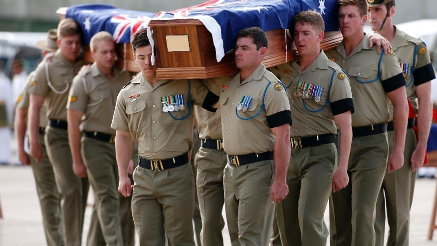 Australian military personnel carry coffins during a repatriation ceremony for Australian soldiers at Subang military air base in Kuala Lumpur, Malaysia, Tuesday, May 31, 2016. The Australian soldiers, many who were casualties during the Vietnam War, were buried in Malaysia along with some dependents. (AP Photo/Vincent Thian)