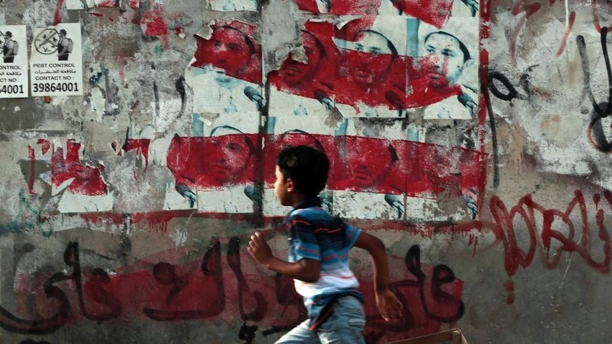 A Bahraini boy runs past a wall with posters showing jailed Shiite cleric Ali Salman, leader of the Al-Wefaq opposition society, that have been painted over by authorities in Malkiya village, Bahrain, Sunday, May 29, 2016. Salman, who is serving a four-year sentence, is to appear in court Monday for a hearing in the appeal of his conviction of inciting disobedience and hatred and insulting an official institution in the Sunni-ruled kingdom. (AP Photo/Hasan Jamali)