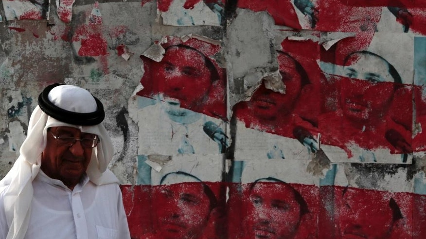 A Bahraini man walks past a wall with posters showing jailed Shiite cleric Ali Salman, leader of the Al-Wefaq opposition society, that have been painted over by authorities in Malkiya village, Bahrain, Sunday, May 29, 2016. Salman, who is serving a four-year sentence, is to appear in court Monday for a hearing in the appeal of his conviction of inciting disobedience and hatred and insulting an official institution in the Sunni-ruled kingdom. (AP Photo/Hasan Jamali)