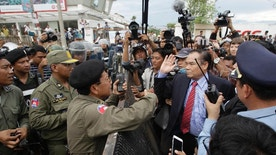 Ho Vann, second right, a lawmaker of Cambodia National Rescue Party (CNRP), talks with police officers near the CNRP headquarters on the outskirts of Phnom Penh, Cambodia, Monday, May 30, 2016. Police in Cambodia blocked an opposition protest march on Monday, but avoided violence by allowing a convoy of opposition lawmakers to drive through to present a petition complaining of government intimidation to the king. (AP Photo/Heng Sinith)