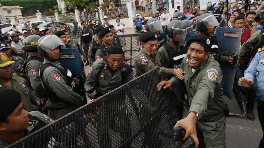 Police officers set up a roadblock on the main street near the Cambodia National Rescue Party (CNRP) headquarters on the outskirts of Phnom Penh, Cambodia, Monday, May 30, 2016. Police in Cambodia blocked an opposition protest march on Monday, but avoided violence by allowing a convoy of opposition lawmakers to drive through to present a petition complaining of government intimidation to the king. (AP Photo/Heng Sinith)
