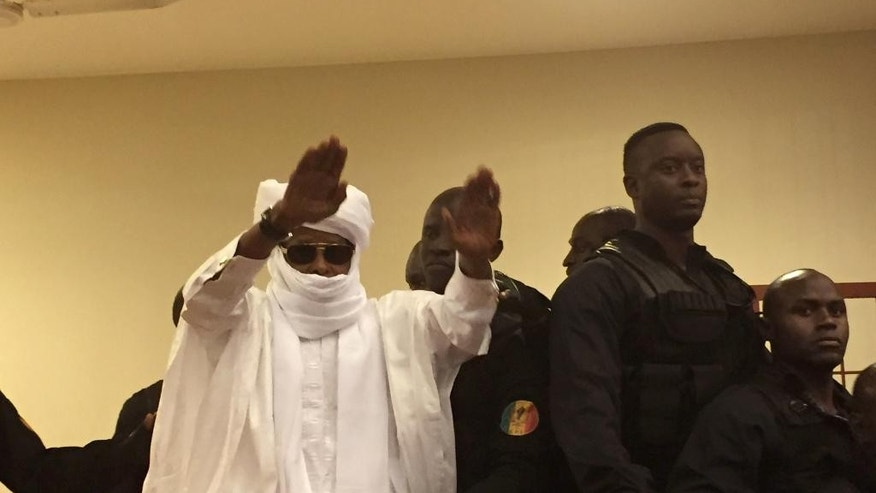 Chad's former dictator Hissene Habre raises his hands after sentencing during court proceedings in Dakar, Senegal, Monday, May 30, 2016.  Judge Gberdao Gustave Kam declared Habre guilty and sentenced him to life in prison for crimes against humanity, war crimes and torture, in a packed courtroom, Monday.(AP Photo/Carley Petesch)