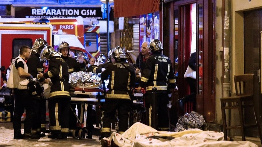 FILE - In this Friday, Nov. 13, 2015 file photo, rescue workers tend to victims in the 10th district of Paris. The jihadi network that recruited and groomed one of the suicide attackers in the Nov. 13 attacks in Paris is on trial, on the week starting Monday, May 30, 2016. Defendants include the brother of Foued Mohamed-Aggad, who joined Islamic State extremists in December 2013 and went on to help carry out the attacks in Paris that left 130 people dead. (AP Photo/Jacques Brinon, file)