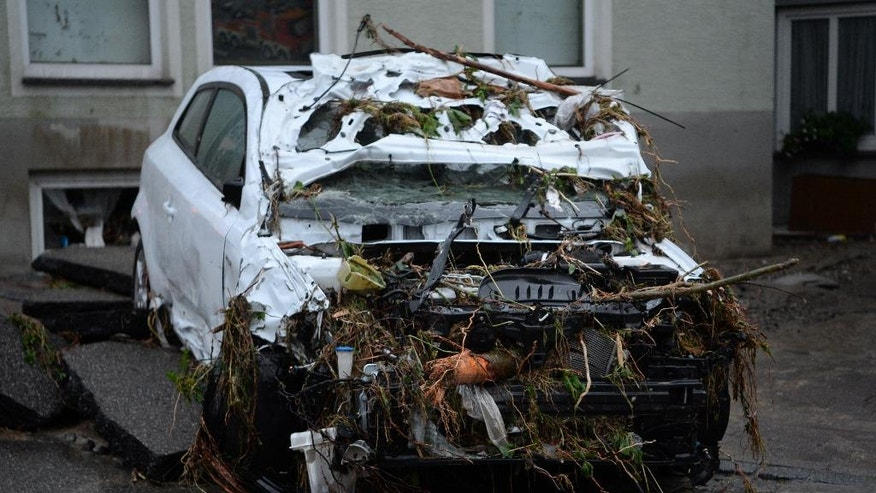 A destroyed car sits in a street in Braunsbach, southwestern Germany, Monday, May 30, 2016.  Authorities said three people are suspected to have died as floods strike southwest Germany. Southern and western Germany, along with other parts of Europe, experienced heavy rainstorms over the weekend.  (Franziska Kraufmann/dpa via AP)