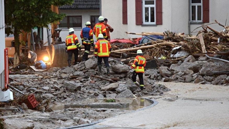 Firefighters climb rubble in a street in Braunsbach, southwestern Germany, Monday, May 30, 2016.  Authorities said three people are suspected to have died as floods strike southwest Germany. Southern and western Germany, along with other parts of Europe, experienced heavy rainstorms over the weekend.  (Franziska Kraufmann/dpa via AP)