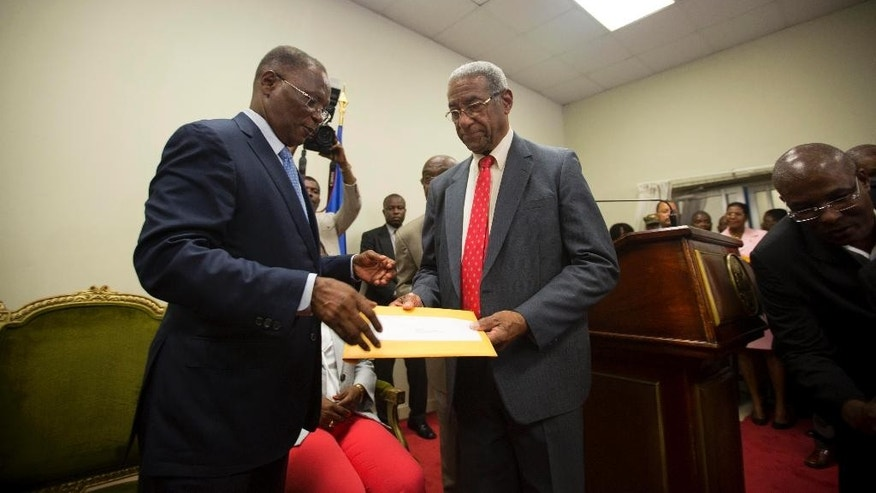 Interim President Jocelerme Privert, left, receives the election report from the president of the verification commission Francois Benoit, at the national palace in Port-au-Prince, Haiti, Monday, May 30, 2016. The commission recommended throwing out the disputed results of last year's first-round presidential election because it appeared to be tainted by fraud. (AP Photo/Dieu Nalio Chery)