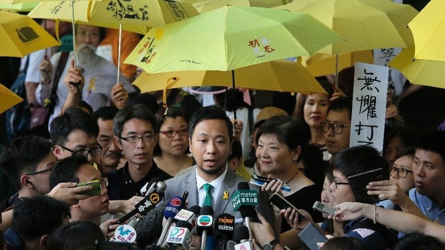Hong Kong activist Ken Tsang, center, talks to reporters while he is surrounded by supporters after a court sentencing hearing in Hong Kong, Monday, May 30, 2016. Tsang whose beating by police was caught on film has been sentenced to prison on charges related to the same confrontation, stirring outrage among pro-democracy supporters. Local news reports said Monday that Tsang was sentenced to five weeks in prison on charges of assaulting police and resisting arrest stemming from the October 2014 incident at the height of street protests that gripped the city. (AP Photo/Vincent Yu)