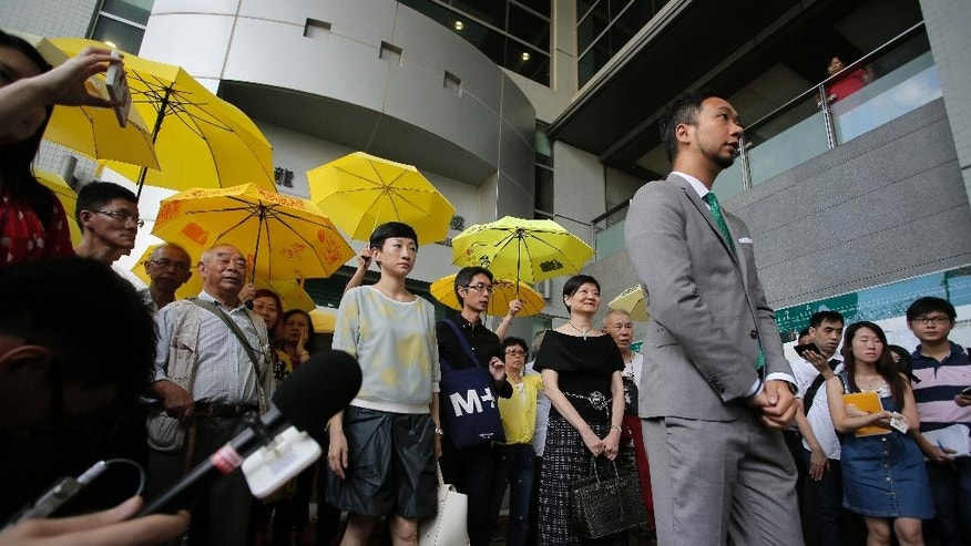 Hong Kong activist Ken Tsang, right, walks out with supporters after a court sentencing hearing in Hong Kong, Monday, May 30, 2016. Tsang whose beating by police was caught on film has been sentenced to prison on charges related to the same confrontation, stirring outrage among pro-democracy supporters. Local news reports said Monday that Tsang was sentenced to five weeks in prison on charges of assaulting police and resisting arrest stemming from the October 2014 incident at the height of street protests that gripped the city. (AP Photo/Vincent Yu)