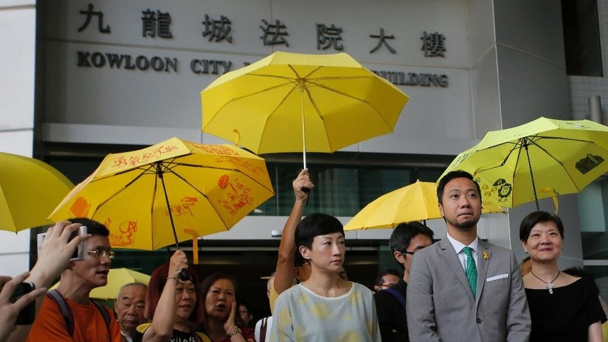 Hong Kong activist Ken Tsang, second from right, talks to reporters after a court sentencing hearing in Hong Kong, Monday, May 30, 2016. Tsang whose beating by police was caught on film has been sentenced to prison on charges related to the same confrontation, stirring outrage among pro-democracy supporters. AP Photo/Vincent Yu)