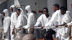 In this photo taken Sunday, May 29, 2016 migrants attend to disembark from the Italian Navy Vega vessel, in Reggio Calabria, southern Italy, after being rescued in the Mediterranean Sea off the coasts of Libya. Survivor accounts have pushed to more than 700 the number of migrants feared dead in Mediterranean Sea shipwrecks over three days in the past week, even as rescue ships saved thousands of others in daring operations. (AP Photo/Adriana Sapone)