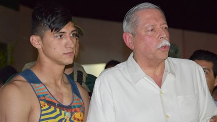Mexican soccer player Alan Pulido, left, stands next to Tamaulipas State Gov. Egidio Torre Cantu after Pulido was rescued from kidnappers early Monday, May 30, 2016 in Ciudad Victoria, the capital of Tamaulipas State, Mexico. Mexican authorities say Pulido, a forward with Olympiacos in the Greek league, has been rescued safe and sound after an hours-long kidnapping in the northeast border state of Tamaulipas. (AP Photo/Alfredo Pena)