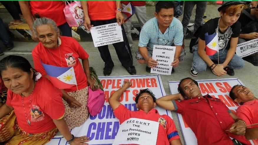 "Supporters of vice presidential candidate Sen. Ferdinand ""Bongbong"" Marcos Jr. hold slogans while sitting and lying on the protest posters during a protest outside the Philippine senate in suburban Pasay, south of Manila, Philippines Monday, May 30, 2016. Marcos, the son of a dictator ousted in a 1986 ""people power"" revolt sparked by widespread human rights abuses and corruption, has raised doubts on the election results of the vice presidential race. (AP Photo/Aaron Favila)"