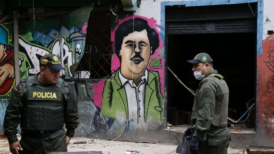 Police officers stand in front of a mural depicting the late drug kingpin Pablo Escobar, in the area known as El Bronx in downtown Bogota, Colombia, Monday, May 30, 2016. Thousands of police officers accompanied by city officials raided early Saturday the area plagued by drug addicts and prostitution. According to Bogota's Major Enrique Penalosa dozens of underage girls who were forced into sexual servitude by gang members were rescued, during the raid. (AP Photo/Fernando Vergara)