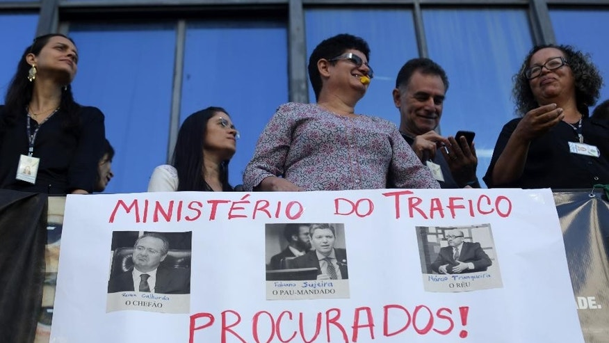 "Ministerial staffers take part in a protest demanding the resignation of the newly-appointed Transparency Minister Fabiano Silveira, pictured in the center of the poster along with Senate President Renan Calheiros, left, with a message that reads in Portuguese; ""Ministry of Illegal Lobbying: Despicable Renan, Big Chief; Dirty Fabiano, Follows Orders; Trickster Narcio Tranquiera, Delinquent  - WANTED!"", at the ministry's headquarters, in Brasilia, Brazil, Monday, May 30, 2016. A recording TV Globo broadcast late Sunday shows Silveira criticizing Operation Car Wash, a wide-ranging corruption probe of the state oil company Petrobras that has implicated numerous leading Brazilian politicians and businessmen.  (AP Photo/Eraldo Peres)"