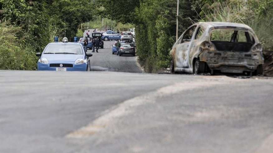 The burned car belonging to slain 22-year-old student Sara Di Pietrantonio is seen along a street in the outskirts of Rome, Monday, May 30, 2016. According to Italian police, Sara, who's body was found close to the car, has been burned alive by her ex-boyfriend as she was was trying to escape from him. (Massimo Percossi/ANSA via AP) ITALY OUT