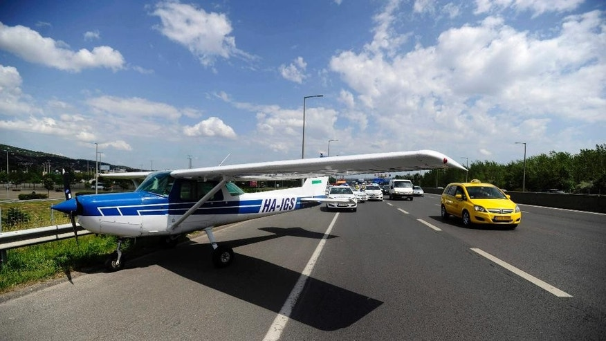 A taxi passes a small aircraft after it made an emergency landing on a busy highway in the outskirts of Budapest, Hungary, Monday, May 30, 2016. An official from a local airport says the Cessna took off on a training flight with two people on board and was forced to land because of engine failure. No injuries were reported. (Zoltan Mihadak/MTI via AP)