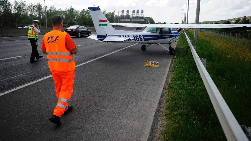 A police officer and a maintenance worker walk toward a small aircraft after it made an emergency landing on a busy highway in the outskirts of Budapest, Hungary, Monday, May 30, 2016. An official from a local airport says the Cessna took off on a training flight with two people on board and was forced to land because of engine failure. No injuries were reported. (Zoltan Mihadak/MTI via AP)
