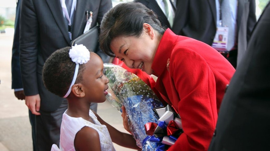 South Korea's president Park Geun-hye receives flowers from Megan Makanga, a grade one pupil of Charm International School, as she arrives at State House in Entebbe, Uganda, Sunday, May 29, 2016. Uganda and South Korea have signed cooperation agreements that officials hope will lead to transfer of technology as Uganda tries to implement an ambitious industrialization program. (AP Photo/Stephen Wandera)