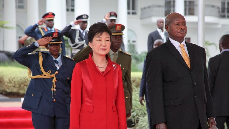 South Korea's president Park Geun-hye, left, and Uganda's President Yoweri Museveni, right, stand for the national anthems at State House in Entebbe, Uganda, Sunday, May 29, 2016. Uganda and South Korea have signed cooperation agreements that officials hope will lead to transfer of technology as Uganda tries to implement an ambitious industrialization program. (AP Photo/Stephen Wandera)
