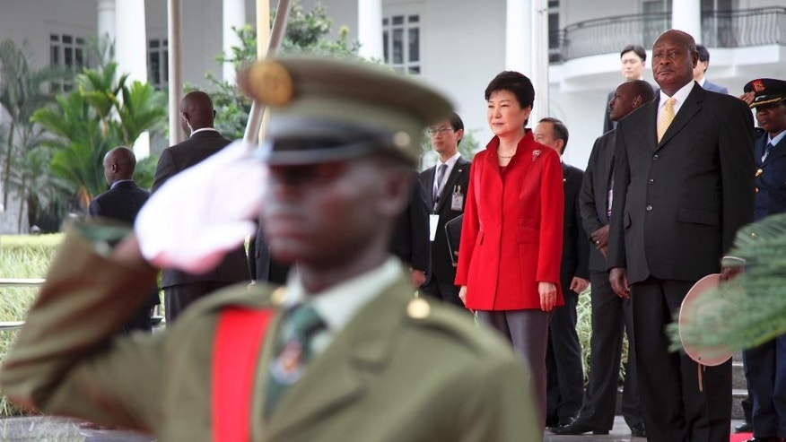 South Korea's president Park Geun-hye, center-right, and Uganda's President Yoweri Museveni, right, stand for the national anthems at State House in Entebbe, Uganda, Sunday, May 29, 2016. Uganda and South Korea have signed cooperation agreements that officials hope will lead to transfer of technology as Uganda tries to implement an ambitious industrialization program. (AP Photo/Stephen Wandera)